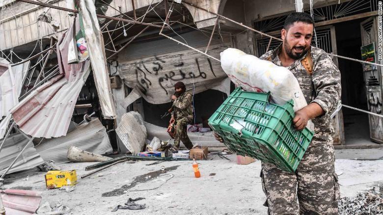 المقاتلون ينهبون المتاجر بعد أن سيطروا على عفرين من القوات الكردية يوم الأحد.