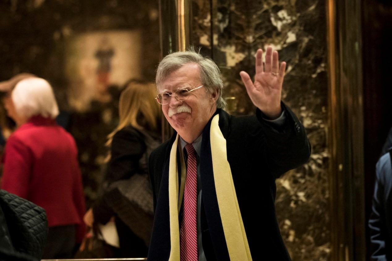 جون بولتون، السفير الأمريكي السابق لدى الأمم المتحدة، يلوّح بينما يغادر برج ترامب في نيويورك في 2 ديسمبر 2016. (درو أنجير / Getty Images)